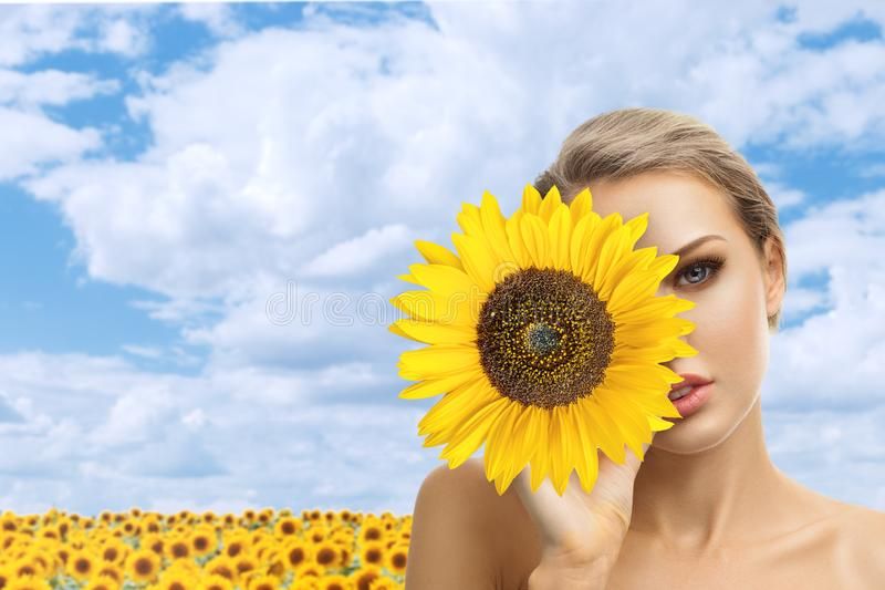Piękna młoda kobieta z słonecznikiem w ona ręki zdjęcia stock