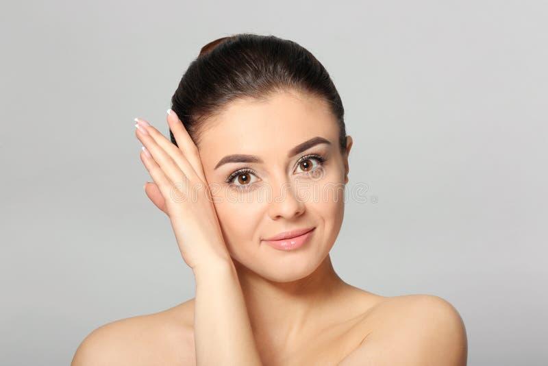 Piękna młoda kobieta z silky skórą po zdroju traktowania na lekkim tle fotografia stock