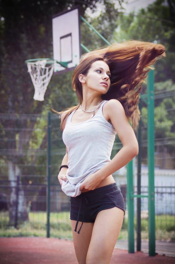 Piękna młoda kobieta z trzepotliwą włosianą bawić się koszykówką outdoors fotografia stock