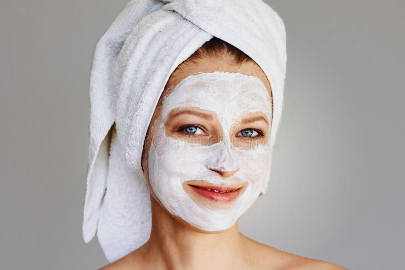 Piękna młoda kobieta z twarzową maską na jej twarzy Skóry traktowanie, opieka, zdrój, naturalny piękno i kosmetologii pojęcie i, fotografia stock