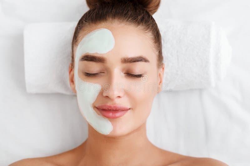 Piękna młoda kobieta z twarzową maską na połówce twarz zdjęcie royalty free
