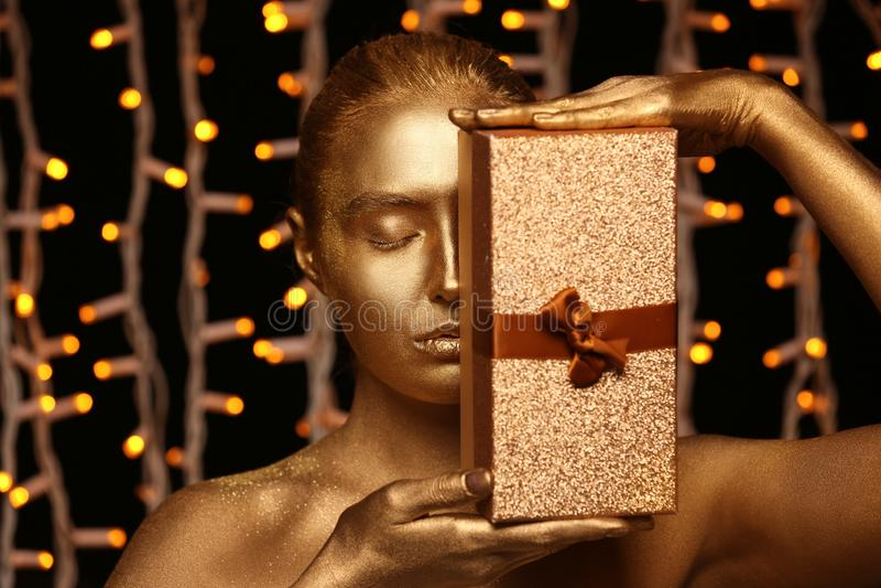 Piękna młoda kobieta z złotą farbą na jej ciała i prezenta pudełku przeciw defocused światłom zdjęcie royalty free