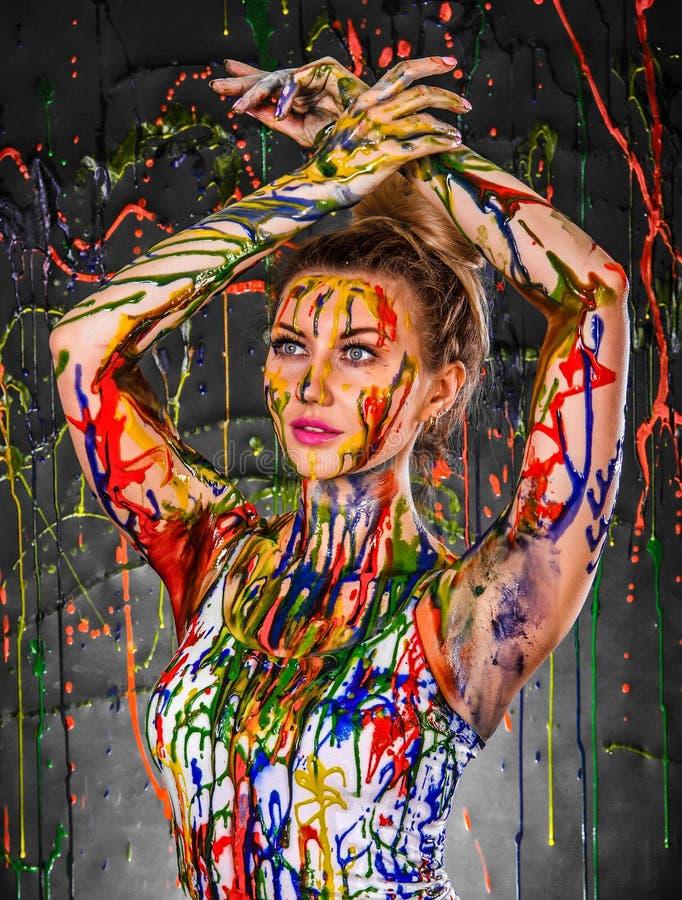 Piękna młoda kobieta zakrywająca z farbami zdjęcie royalty free
