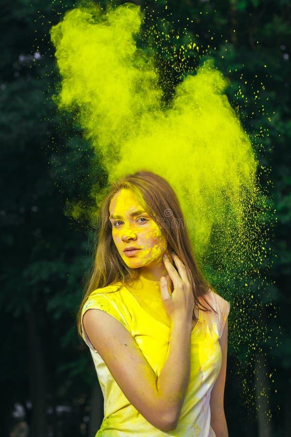Piękna młoda kobieta zakrywający kolor żółty farby suchy holi obraz royalty free