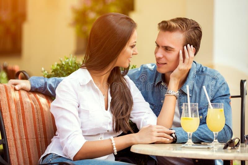 Piękna młoda kochająca para siedzi wpólnie w kawiarni obraz stock