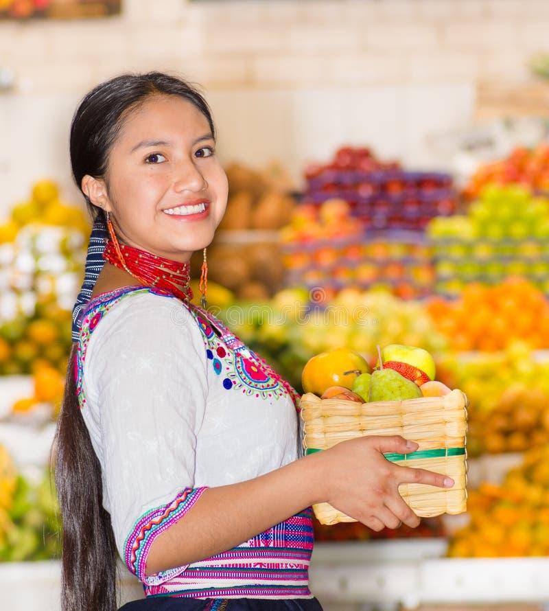 Piękna młoda latynoska kobieta jest ubranym andyjską tradycyjną bluzkę pozuje dla kamery mienia kosza fuits wśrodku owoc fotografia royalty free