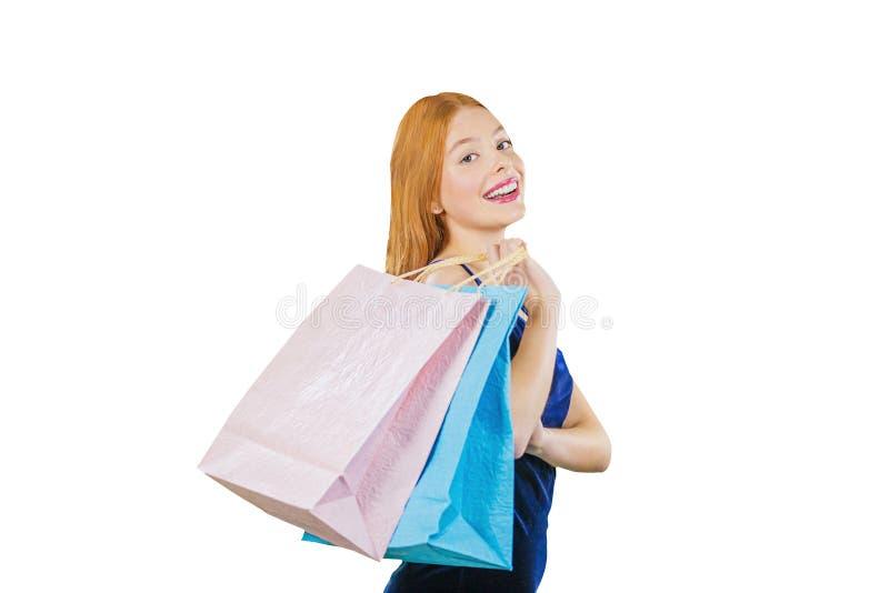 Piękna młoda miedzianowłosa dziewczyna w sukni trzyma trzy pakunku rzuca one na jej ramieniu i patrzeje nad ona, obraz stock
