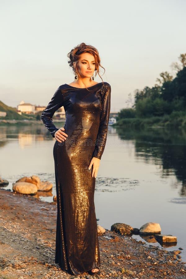 Piękna młoda modna kobieta pozuje w sukni przy rzecznym wybrzeżem obraz royalty free