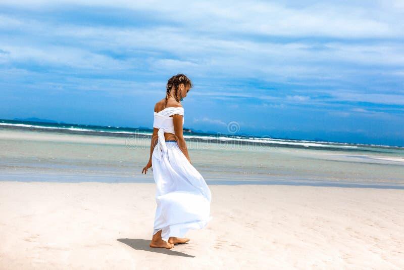 Piękna młoda modna kobieta w biel sukni odprowadzeniu zdjęcie stock