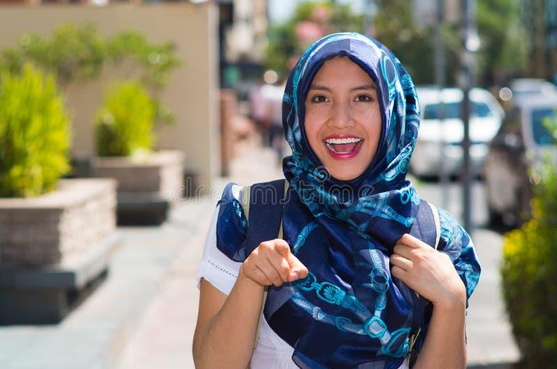 Piękna młoda muzułmańska kobieta jest ubranym błękitnego barwionego hijab, wskazuje palcowy ono uśmiecha się, outdoors miastowy t fotografia stock
