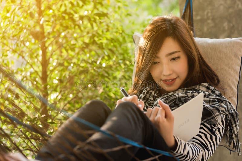 Piękna młoda nastoletnia kobieta pisze notatce dla 2018 w białym noteb zdjęcie royalty free