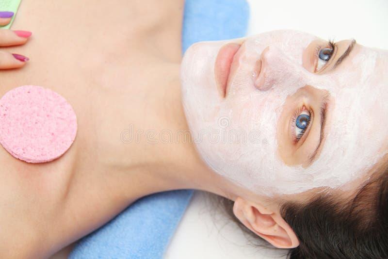 Piękna młoda niebieskie oko kobieta z glinianą twarzową maską obrazy stock