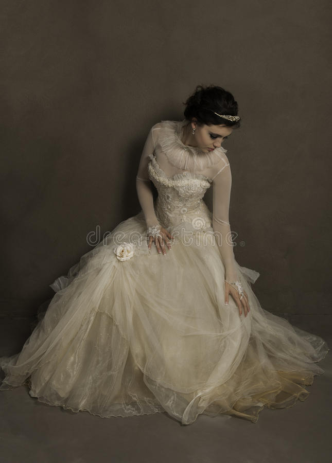 Piękna młoda panna młoda osiedla jej rocznik ślubną suknię fotografia stock