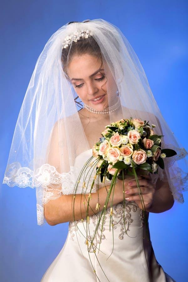 Piękna młoda panna młoda w przesłonie i suknia na Błękitnym tle nagi zdjęcia royalty free