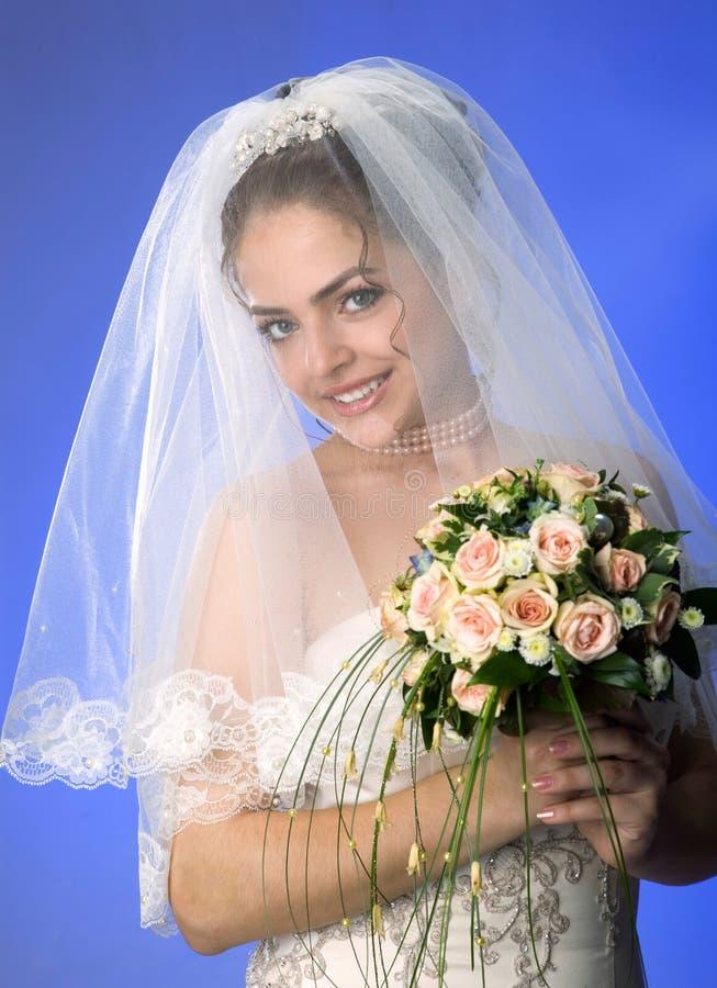 Piękna młoda panna młoda w przesłonie i suknia na Błękitnym tle nagi obraz stock