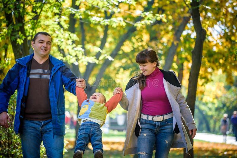 Piękna młoda rodzina na spacerze w jesień lesie na klonowym żółtym drzewa tle ojciec ręce złap matki syn Szczęśliwy obraz stock