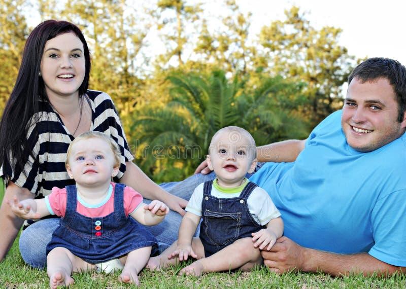 Piękna młoda rodzina z bliźniaczymi dziećmi fotografia stock