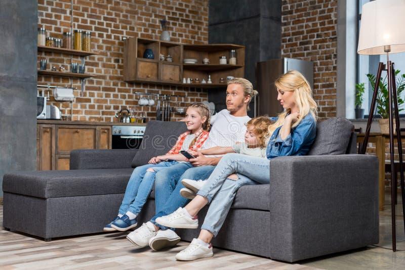 piękna młoda rodzina z dwa dzieciakami ogląda tv zdjęcie royalty free