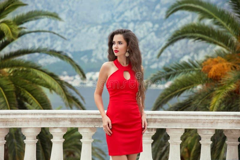 Piękna młoda seksowna brunetki dziewczyna w czerwieni smokingowy pozować na Balcon obrazy royalty free