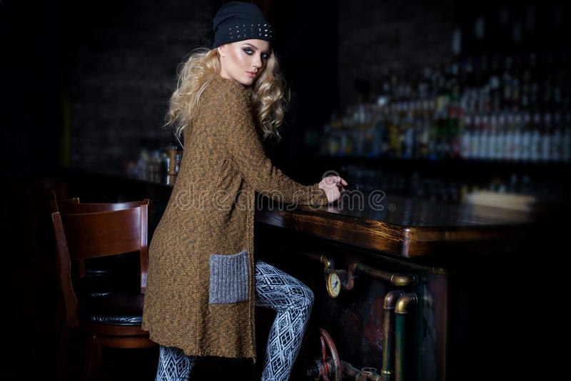 Piękna młoda seksowna kobieta z długim blondynem, jaskrawy makijaż Smokey ono Przygląda się będący ubranym pulower obok dresser i fotografia royalty free