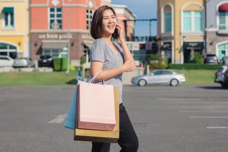 Piękna młoda shopaholic Azjatycka kobieta używa smartphone dla opowiadać podczas gdy chodzi kupować kosmetyki, odziewa etc obrazy royalty free