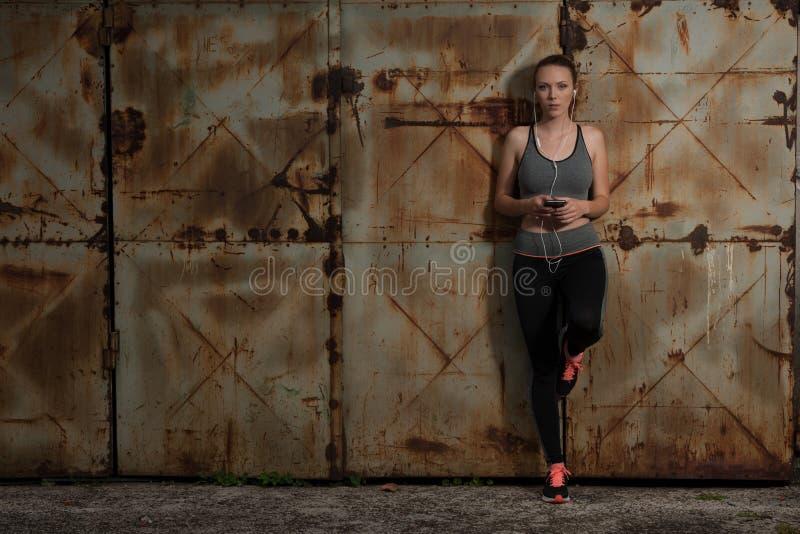 Piękna młoda sporty kobieta słucha muzykę i relaksuje blisko ośniedziałego i obrazy stock