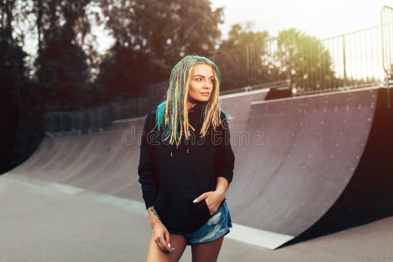Piękna młoda sprawności fizycznej kobieta w czarnym hoodie pozyci łyżwy parku zdjęcie royalty free
