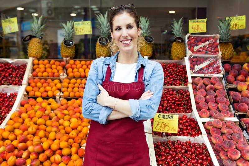 Piękna młoda sprzedawczyni patrzeje kamerę w zdrowie sklepu spożywczego sklepie zdjęcie stock