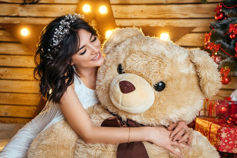 Piękna młoda szczęśliwa kobieta w świątecznym trybowym czekać na nowym roku i bożych narodzeniach siedzi z dużym zabawka niedźwie obrazy stock