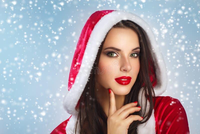 Piękna młoda szczęśliwa kobieta w Święty Mikołaj odziewa nad Bożenarodzeniowym tłem tło nad uśmiechniętą białą kobietą piękna odo fotografia royalty free