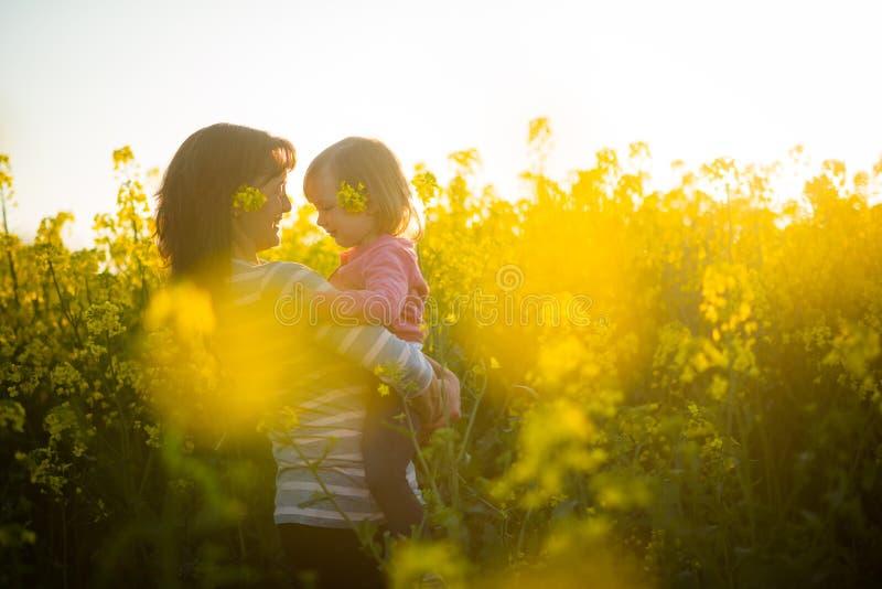 Piękna młoda uśmiechnięta kobieta na rapeseed polu z dzieckiem zdjęcia royalty free