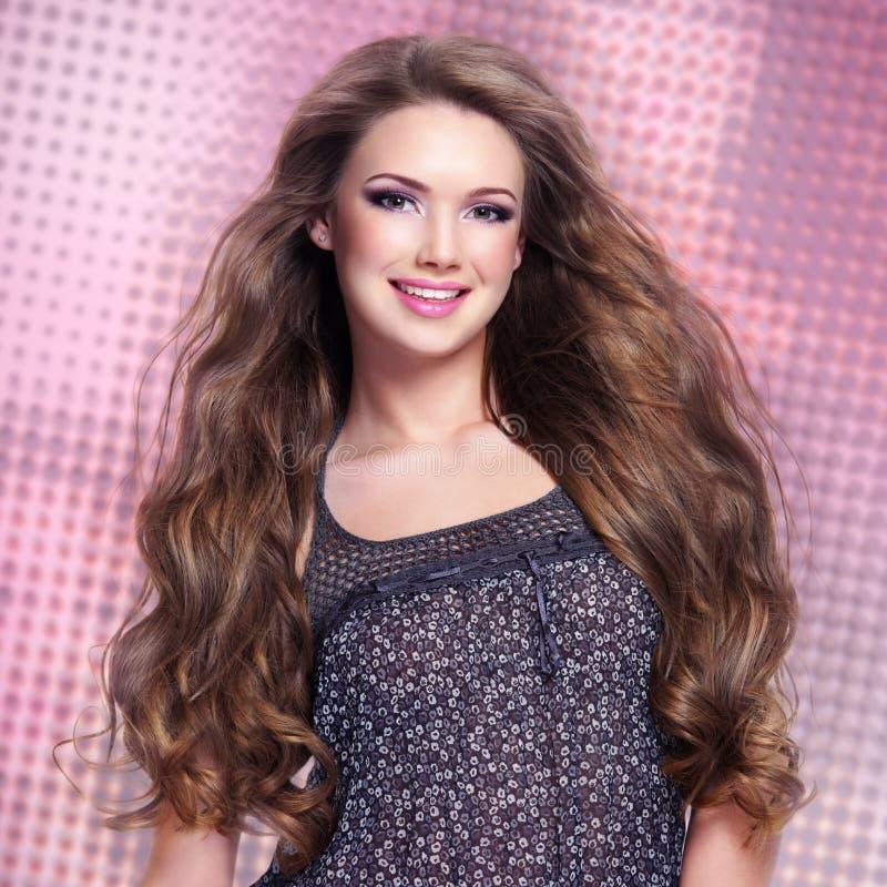 Piękna młoda uśmiechnięta kobieta patrzeje kamerę z długimi hairs zdjęcia stock