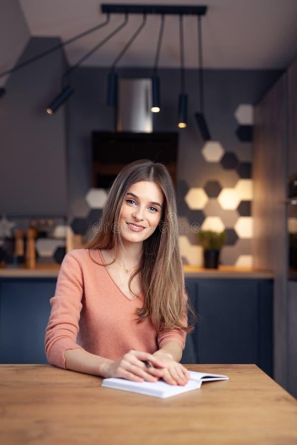 Piękna młoda uśmiechnięta kobieta pracuje od domu obraz stock