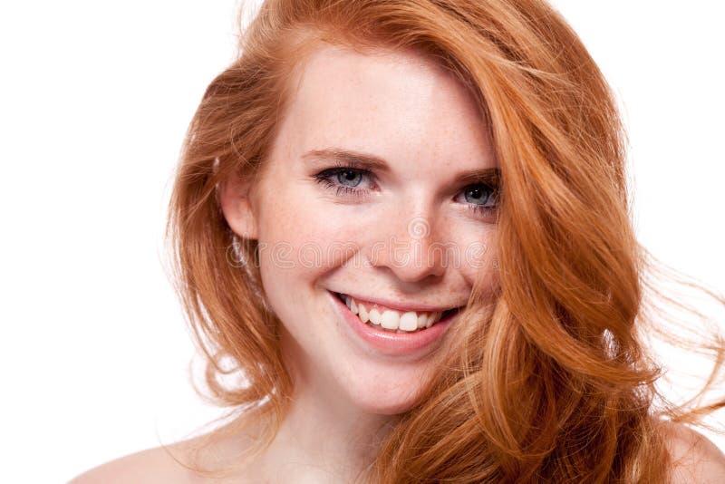 Piękna młoda uśmiechnięta kobieta z czerwonym włosy i piegami odizolowywającymi fotografia stock