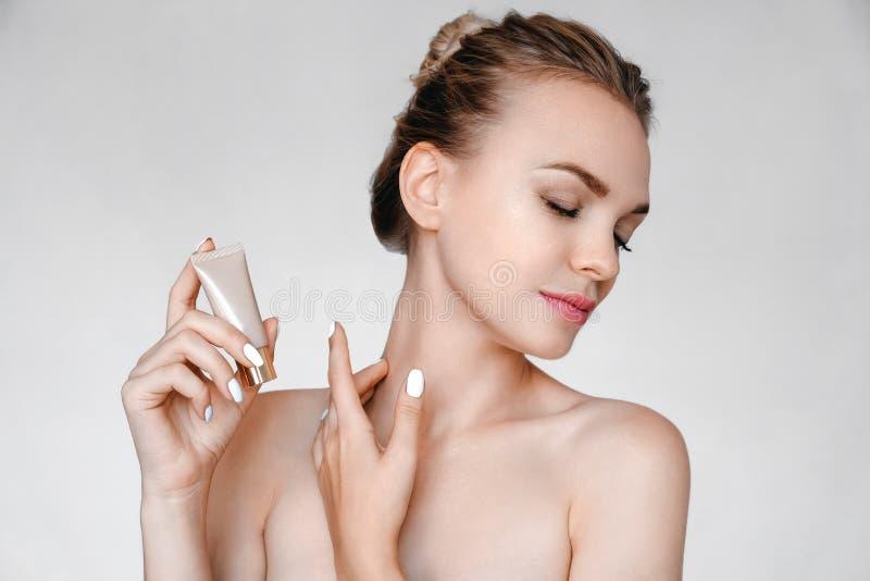 Piękna młodej kobiety mienia twarzy śmietanka Twarzowy traktowanie Kosmetologia, pi?kno i zdr?j, obrazy stock