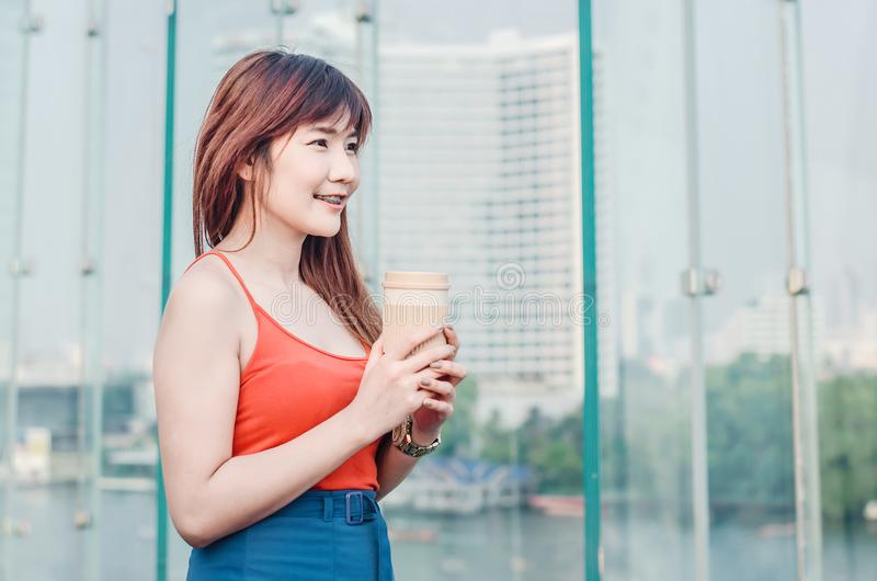 Piękna młodej kobiety pozycja na balkonowym mieć filiżanka kawy, cieszy się słońce na gorącym letnim dniu Azja kobieta na tarasie fotografia stock