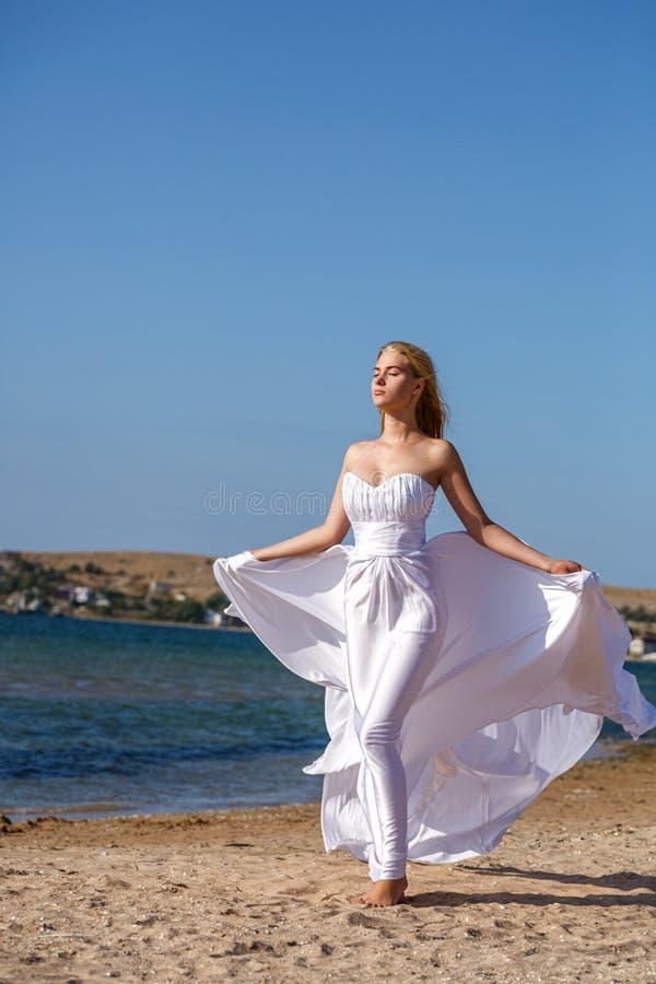 Piękna młodej kobiety pozycja w biel sukni morzem na słonecznym dniu obraz royalty free
