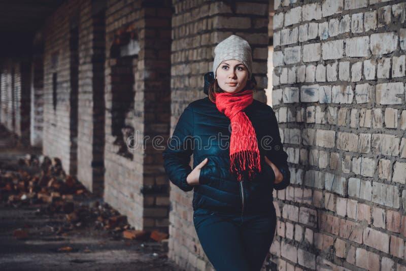 Piękna młodej kobiety pozycja w zniszczonym budynku w zimnym tonięciu zdjęcie stock