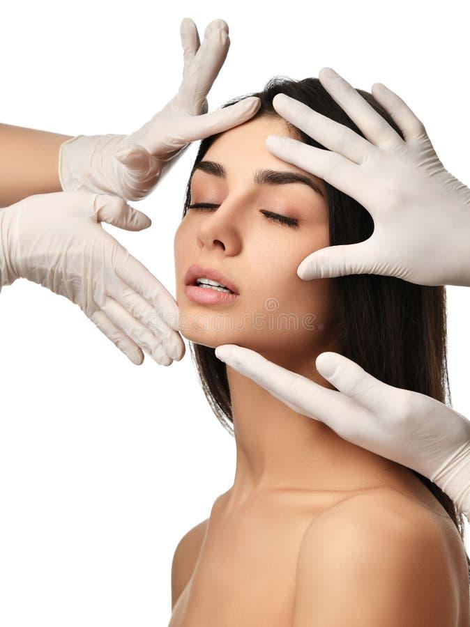 Piękna młodej kobiety twarz z zamkniętymi oczami po chirurgii plastycznej i lekarki ręk w medycznych rękawiczkach fotografia royalty free