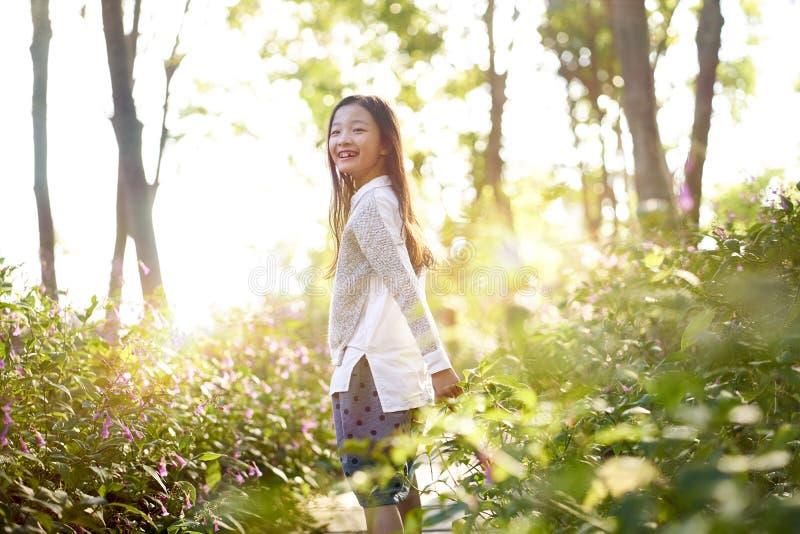 Piękna mała azjatykcia dziewczyny pozycja w kwiatu polu fotografia stock