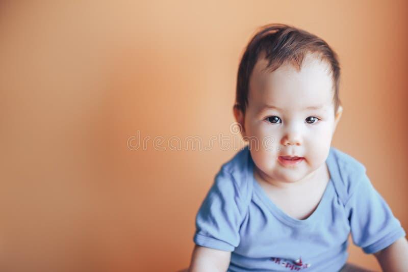 Piękna mała dziewczyna lub chłopiec z ciemnym włosy ono uśmiecha się na jaskrawym pomarańczowym tła colour 2019 z przestrzenią dl obrazy royalty free
