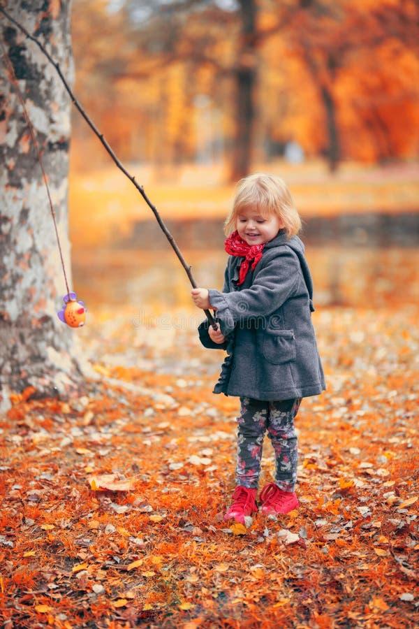Piękna mała dziewczynka bawić się połów z gałąź i ryba zabawką obraz stock