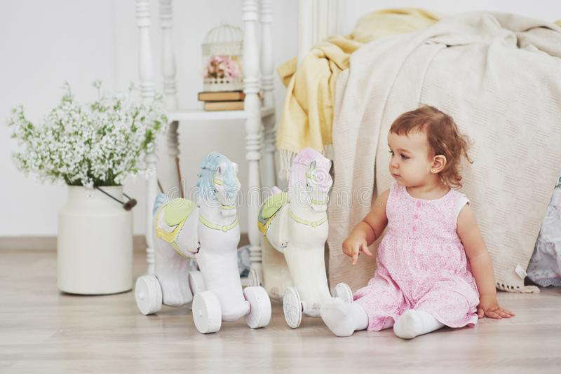 Piękna mała dziewczynka bawić się zabawki niebieski się blondynki Biały krzesło Dziecka ` s pokój Szczęśliwy mały dziewczyna port zdjęcia royalty free