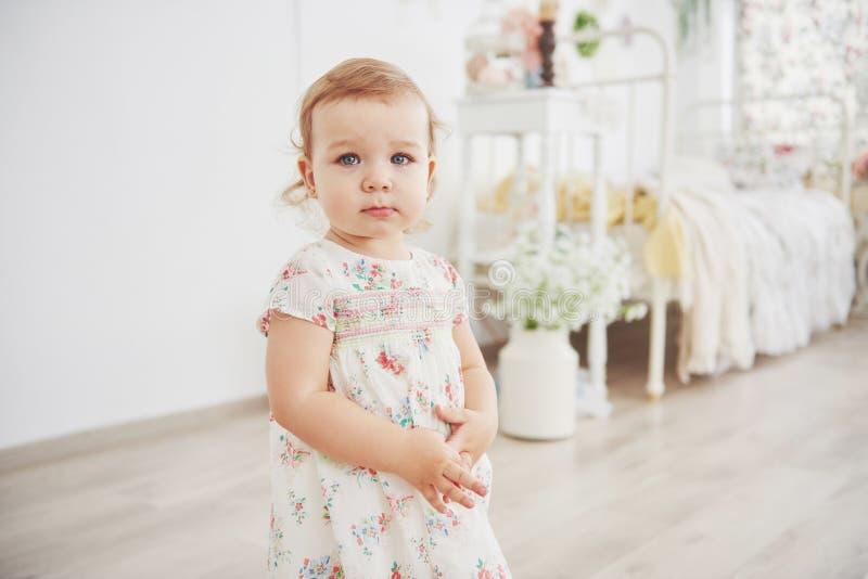 Piękna mała dziewczynka bawić się zabawki niebieski się blondynki Biały krzesło Dziecka ` s pokój Szczęśliwy mały dziewczyna port obrazy royalty free
