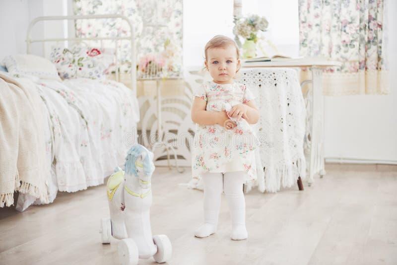 Piękna mała dziewczynka bawić się zabawki niebieski się blondynki Biały krzesło Dziecka ` s pokój Szczęśliwy mały dziewczyna port zdjęcie stock