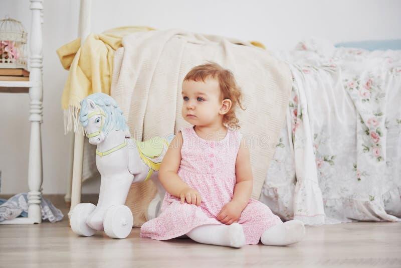 Piękna mała dziewczynka bawić się zabawki niebieski się blondynki Biały krzesło Dziecka ` s pokój Szczęśliwy mały dziewczyna port fotografia stock