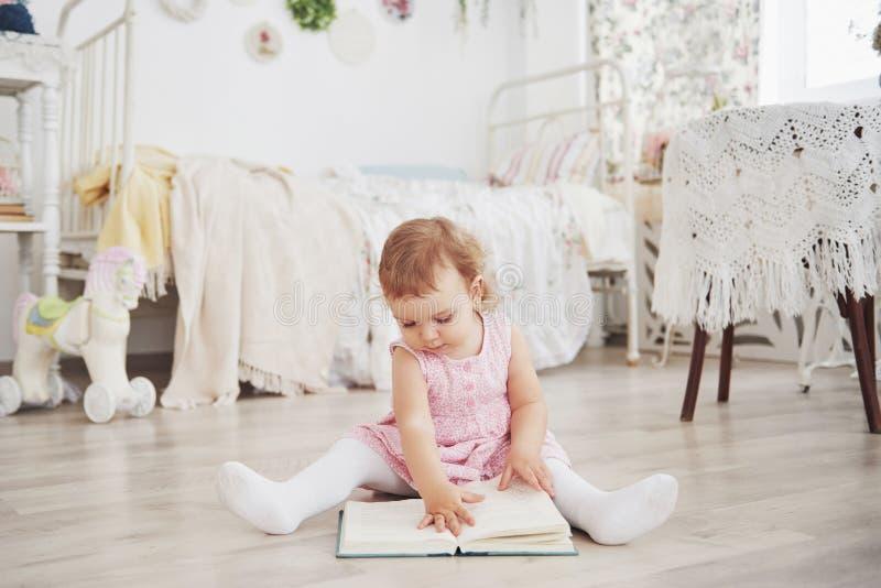 Piękna mała dziewczynka bawić się zabawki niebieski się blondynki Biały krzesło Dziecka ` s pokój Szczęśliwy mały dziewczyna port fotografia royalty free