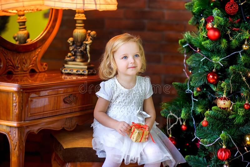 Piękna mała dziewczynka blisko świątecznego choinki mienia prezenta zdjęcia royalty free