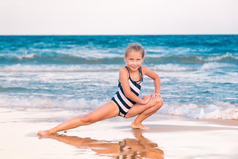Piękna mała dziewczynka excercising na plaży zdjęcie stock