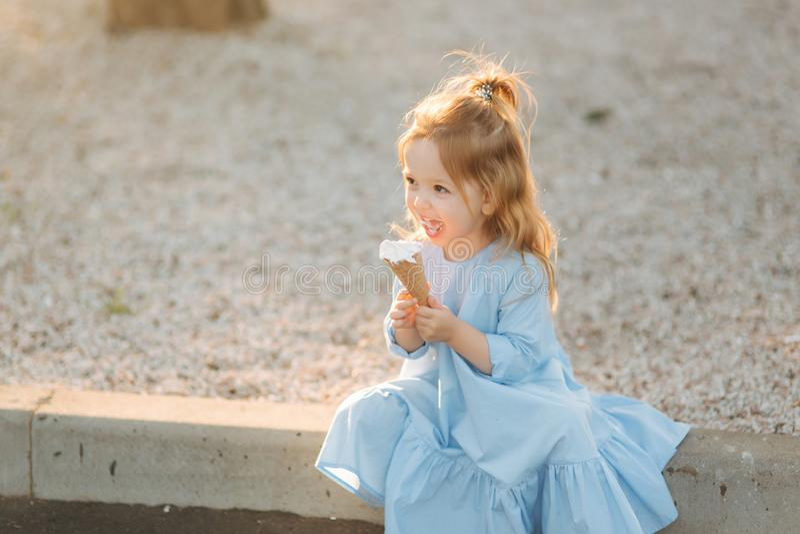 Piękna mała dziewczynka je lody w błękitnej sukni obraz royalty free